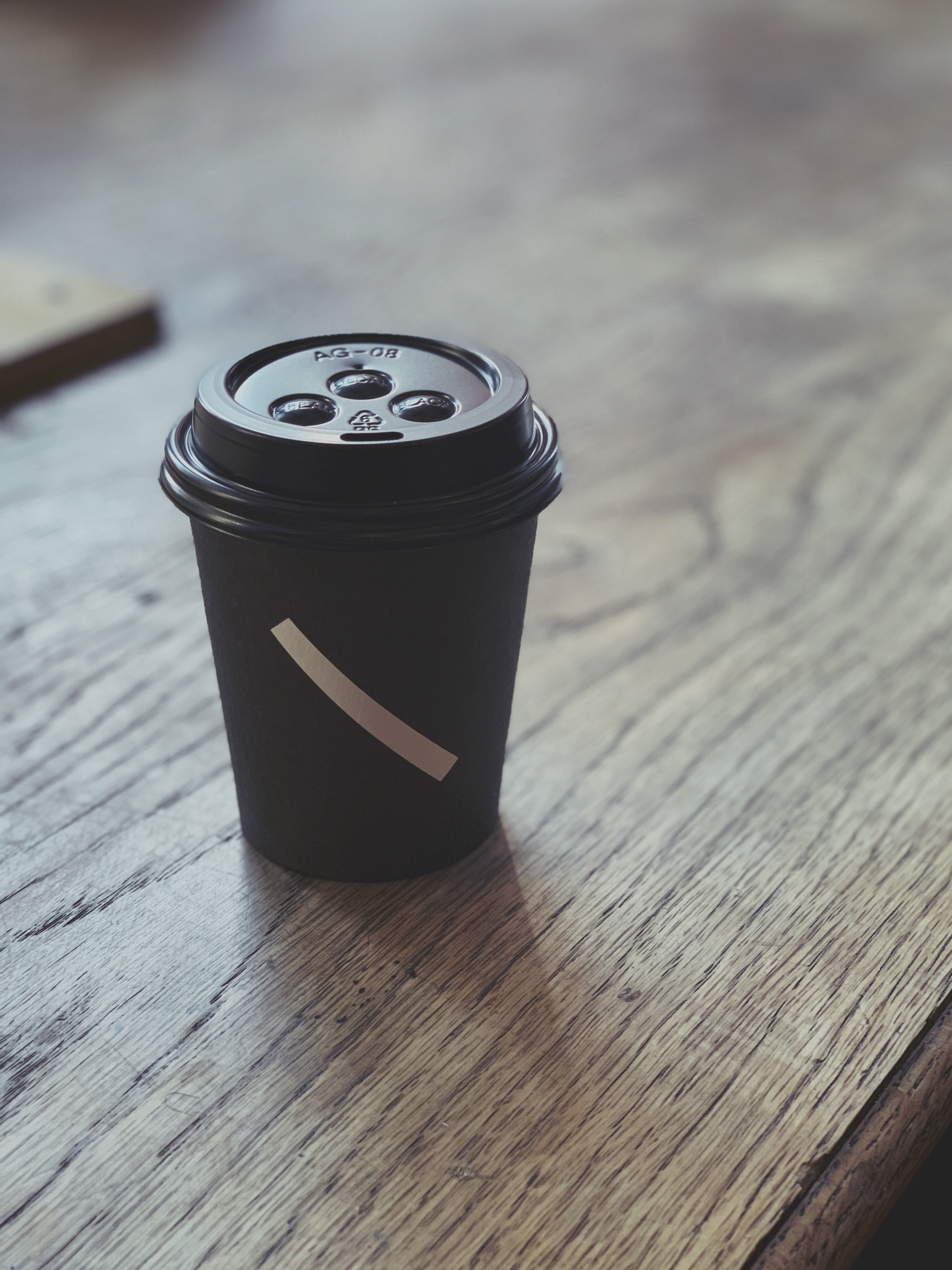 black plastic disposable cup on brown surface