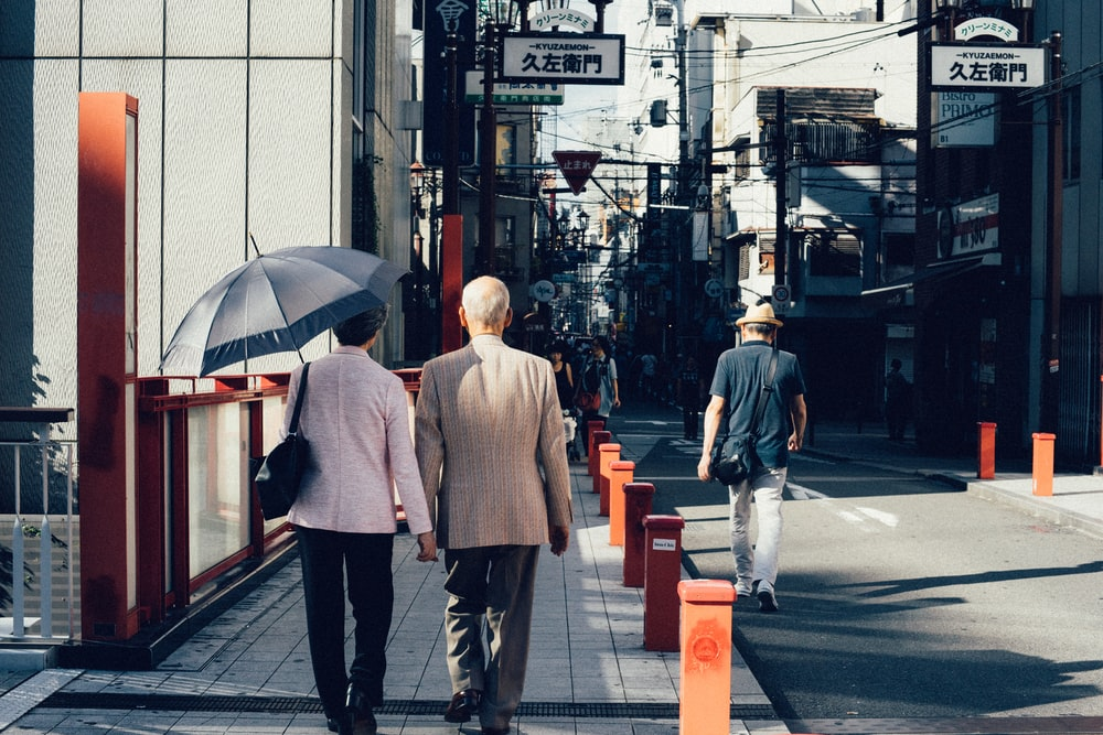 man and woman walking on concrete walkway