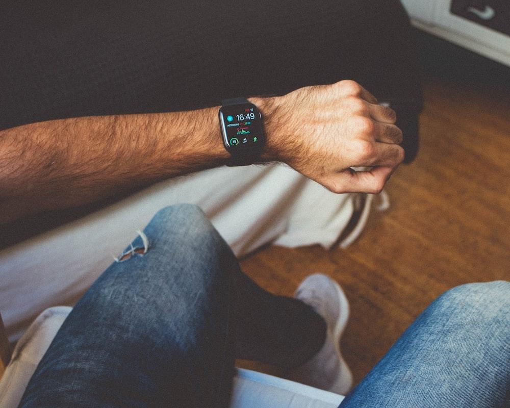 sitting man in blue denim jeans showing smartwatch