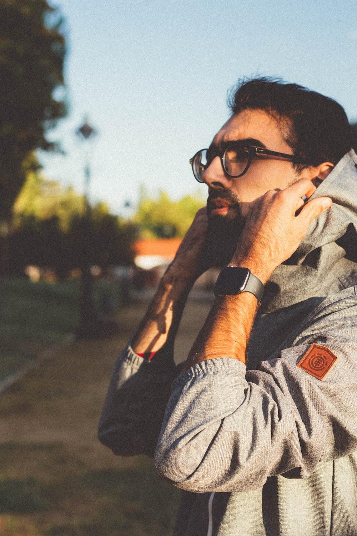 man wearing black framed eyeglasses fixing hood
