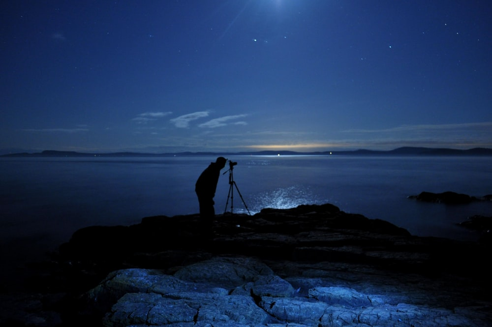 man taking photo with camera on tripod in beach