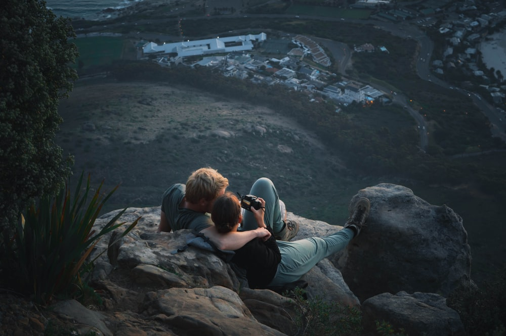 two person sitting on rocks