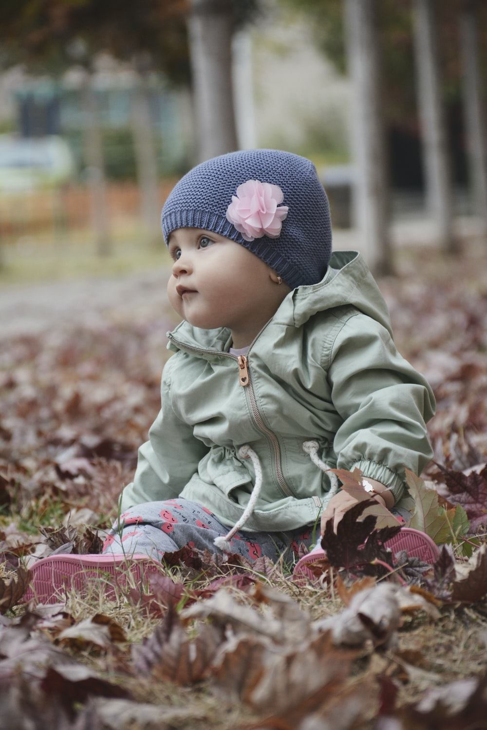 baby wearing gray beanie cap sitting surrounded by dried leaves