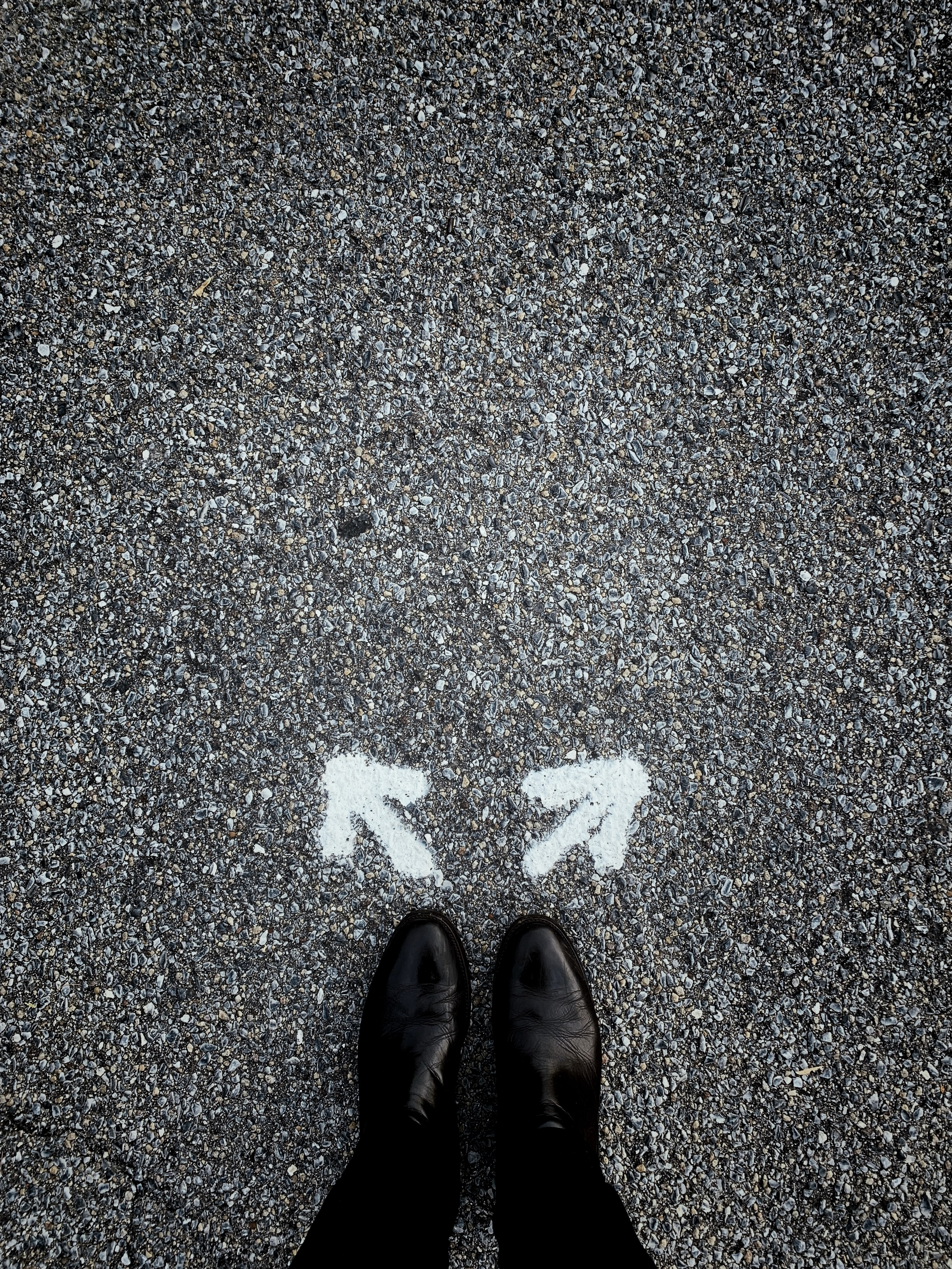 Person standing on concrete with arrows pointing in opposite directions