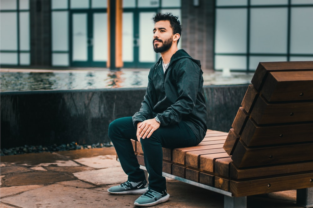 man sitting on wooden lounge