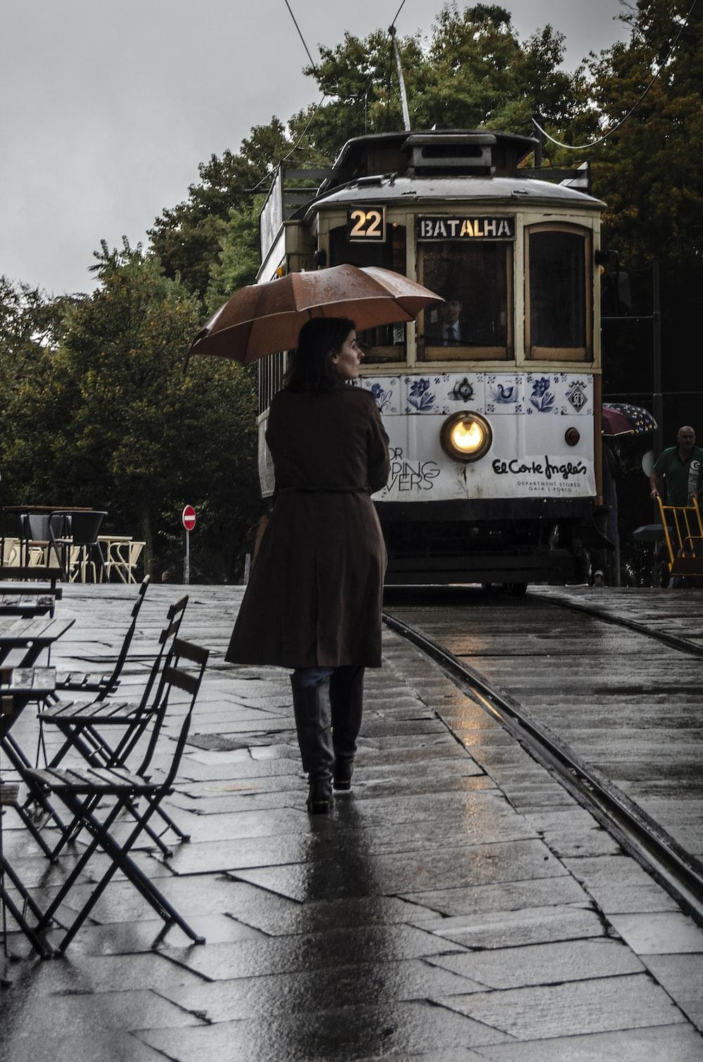 woman wearing brown coat walking on street while holding umbrella