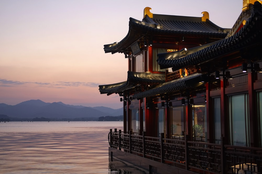 brown and red temple beside water