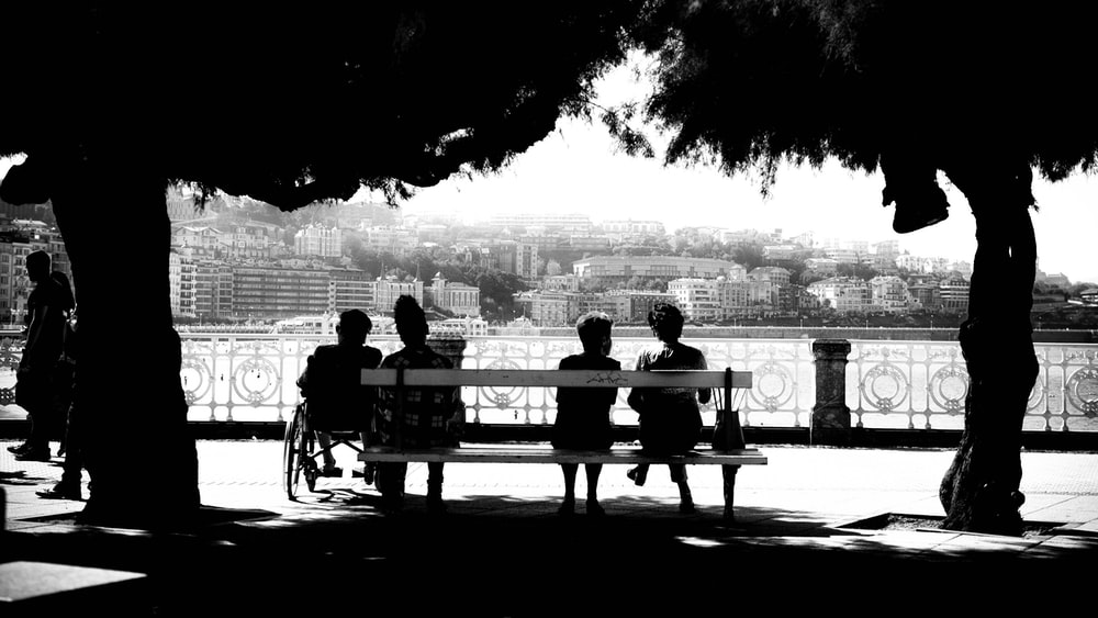 four people sitting on bench
