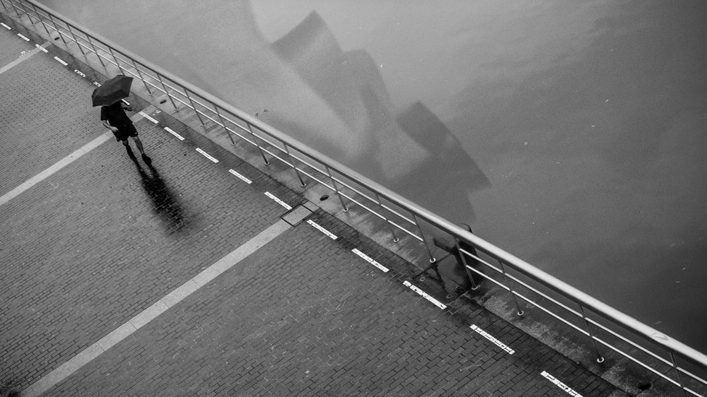 grayscale photography of person walking with umbrella
