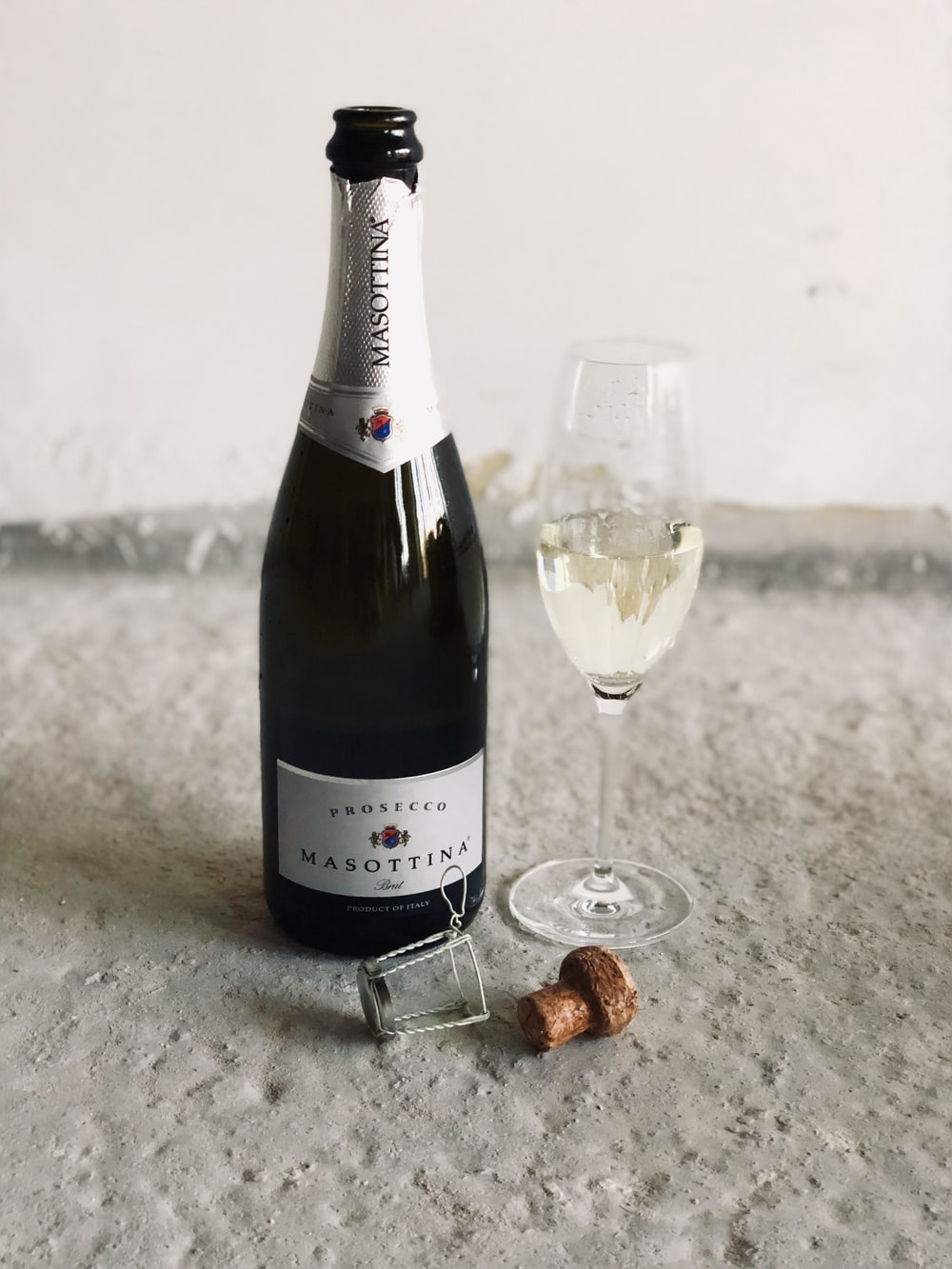black champagne bottle beside champagne flute