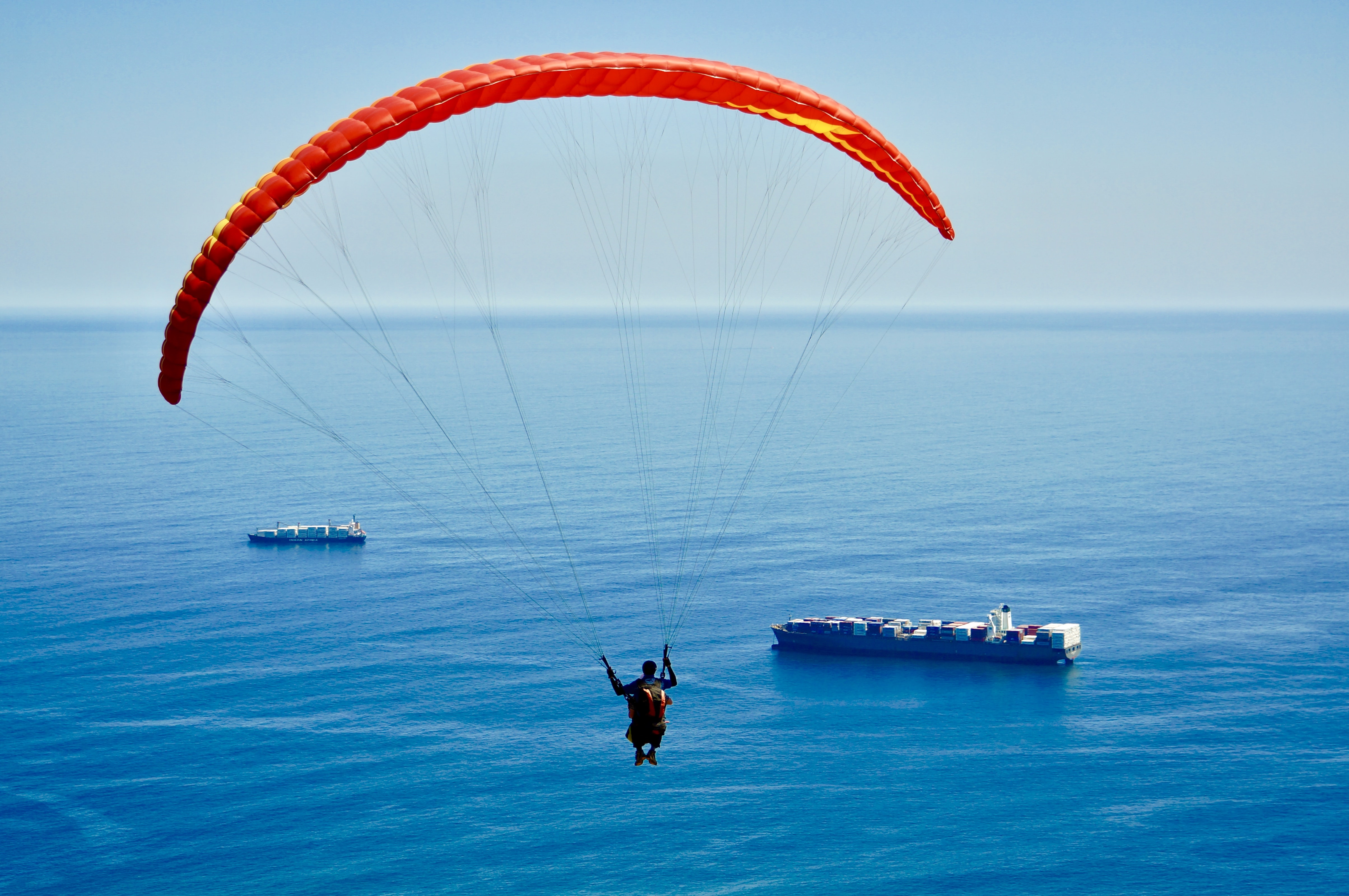 man on parachute above sea