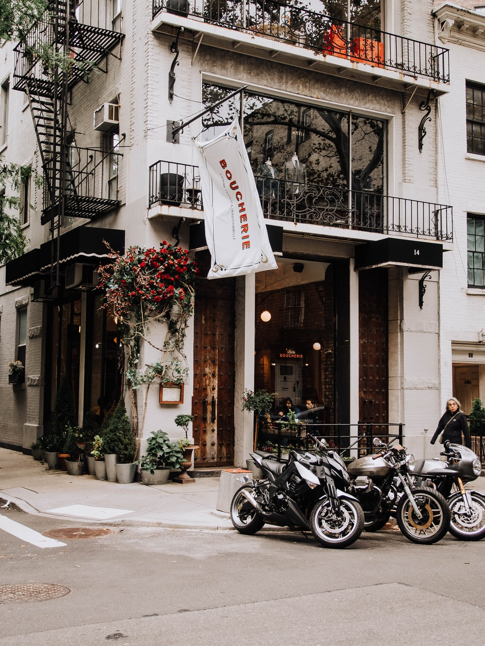 three motorcycles parked near white building