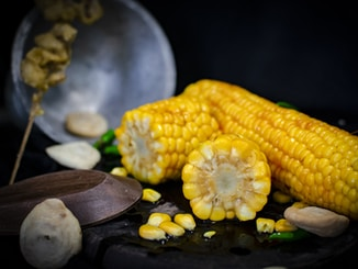 selective focus photography of three yellow corns