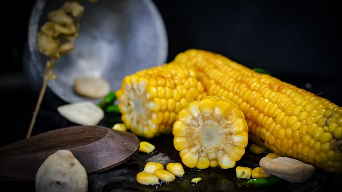 selective focus photography of three yellow corns