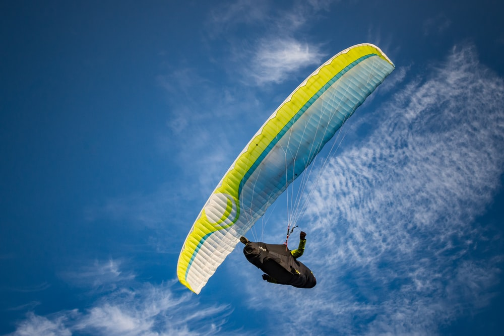person on yellow and white parachute