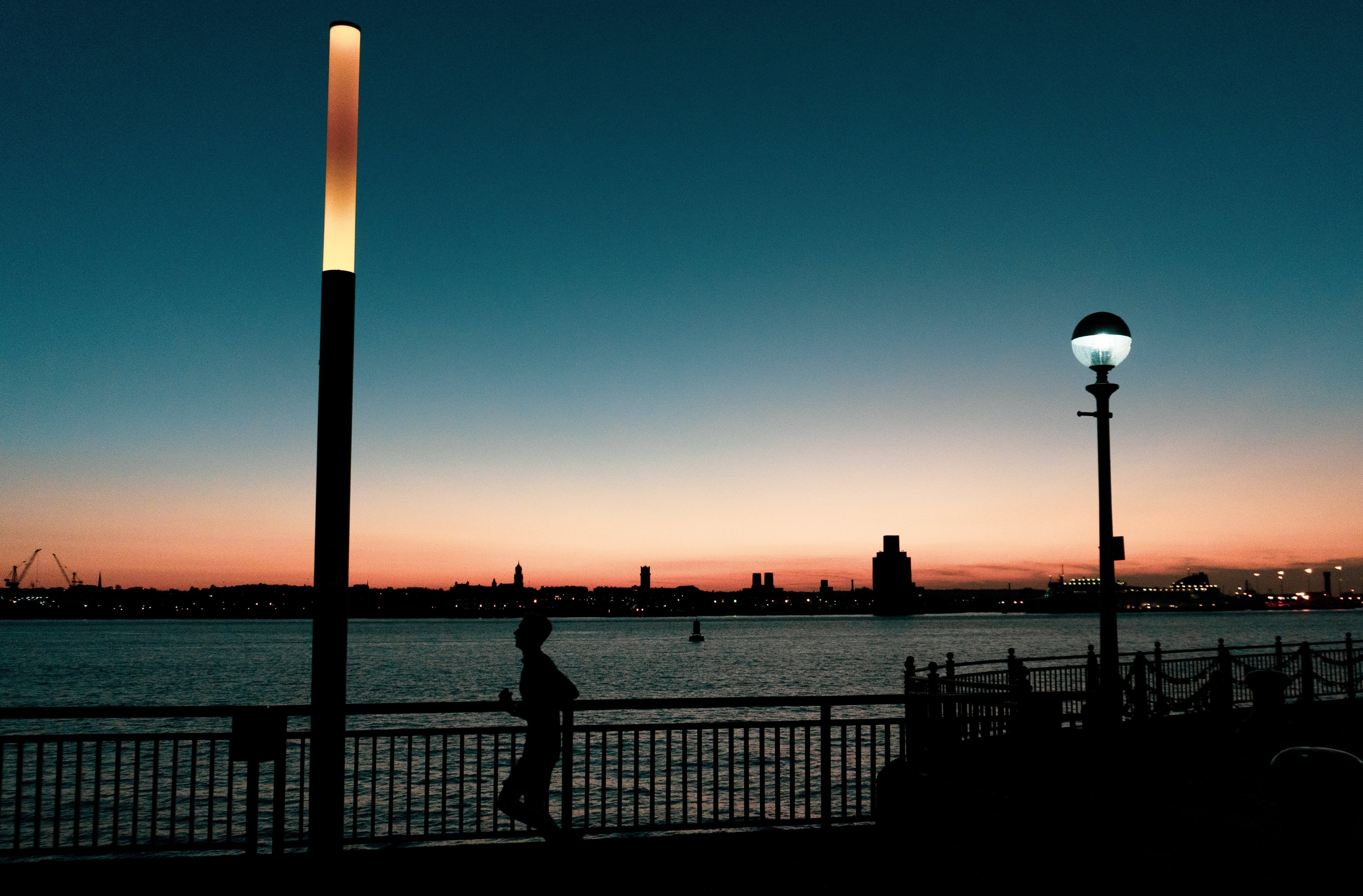 silhouette of man jogging near body of water
