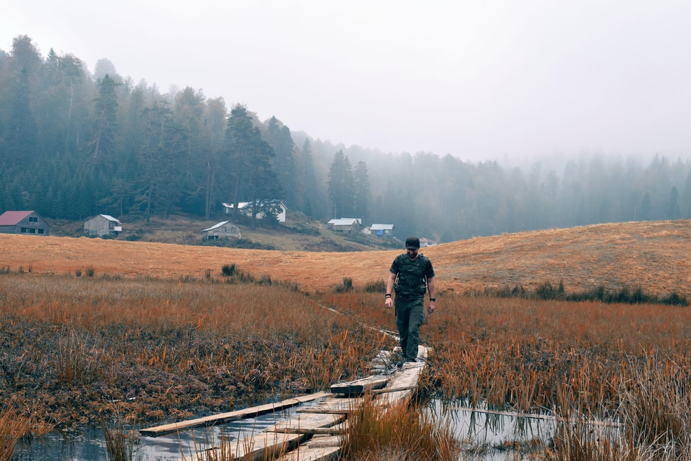 man wearing black shirt walking on brown bridge