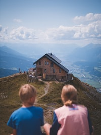 boy and girl sitting on cliff overlooking house at daytime