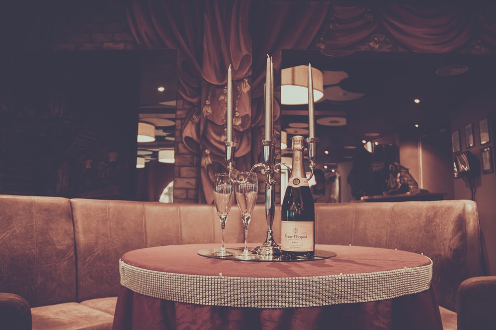 wine bottle, wine glass, and candle on round table