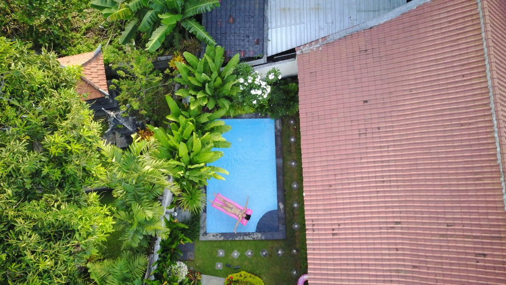 top view of woman lying on pink swimming bed at at swimming pool