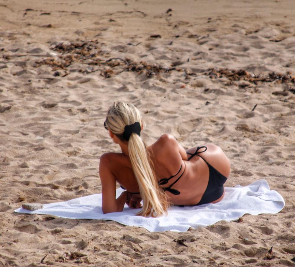 woman lying on white towel