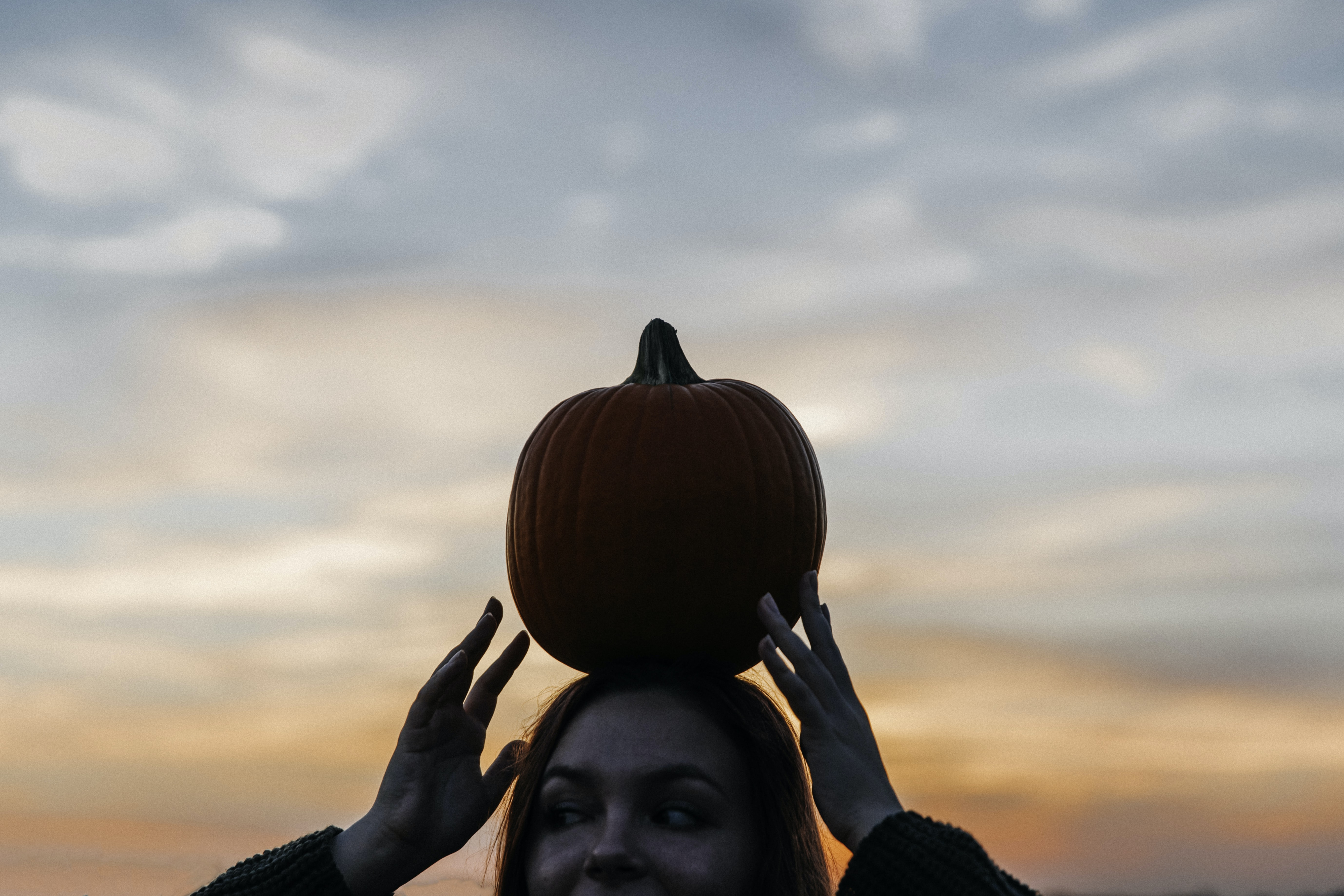 woman carrying pumpkin on head