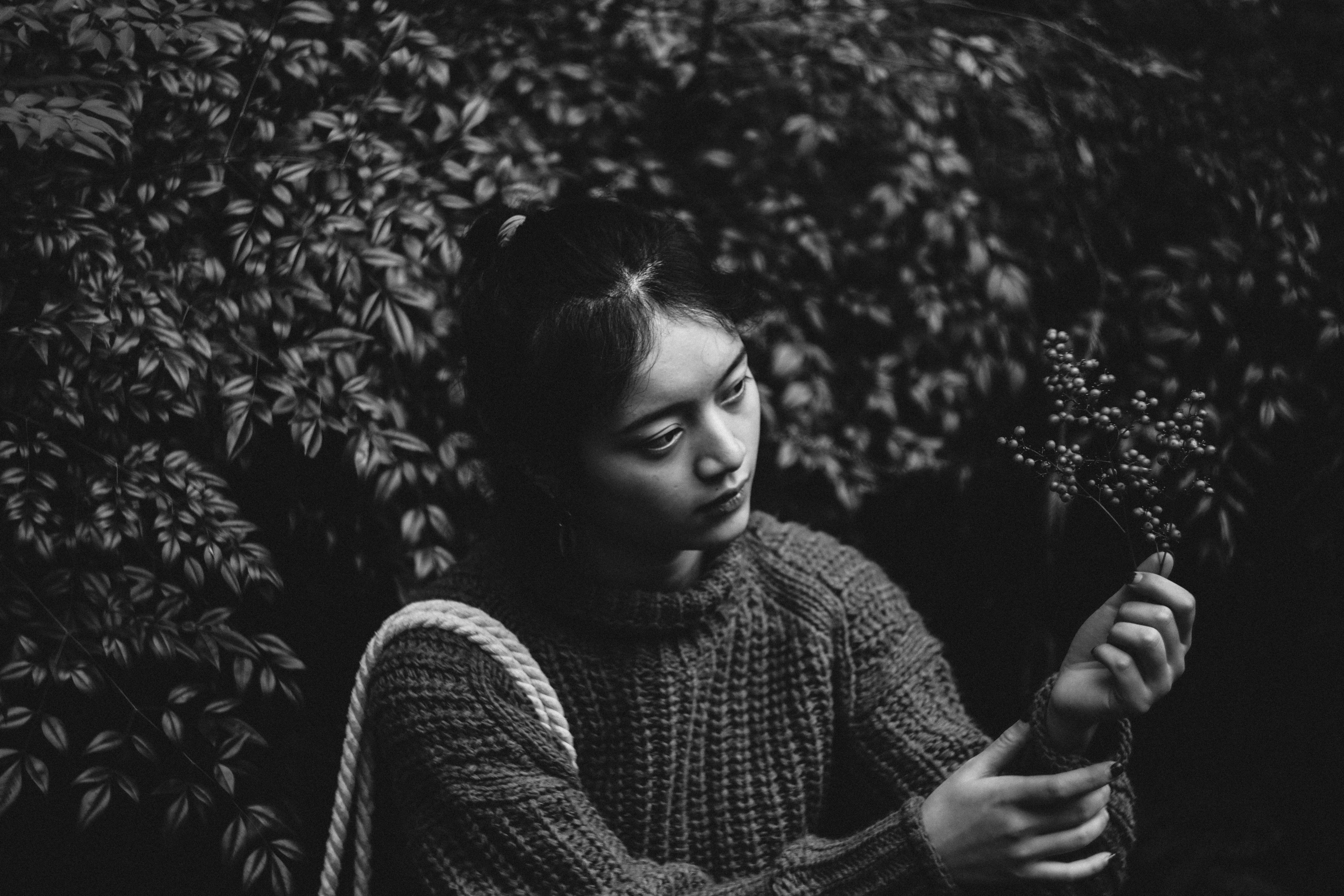 grayscale photography of woman holding leaf