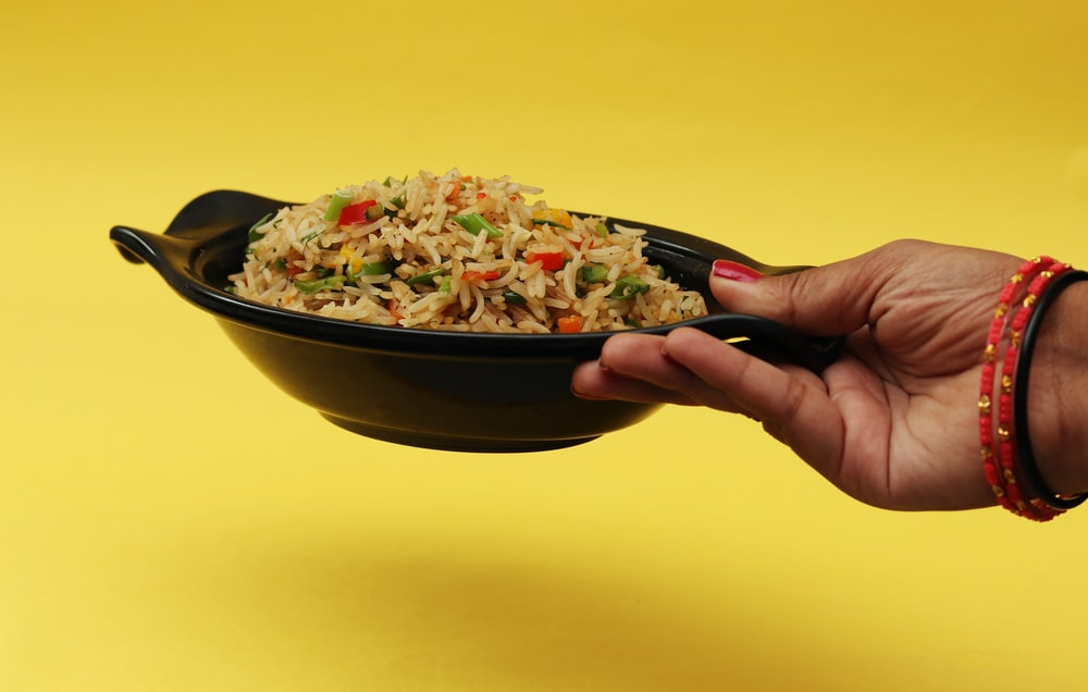 person holding black ceramic bowl with rice