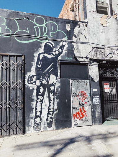 man holding skateboard graffiti during daytime