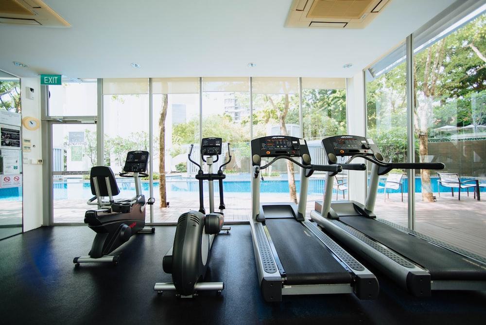 black and grey treadmill and stationary bikes