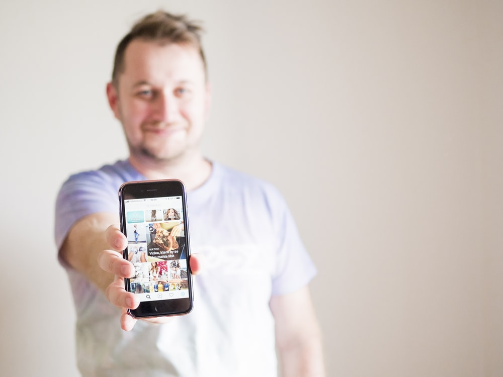 man wearing grey shirt holding smartphone