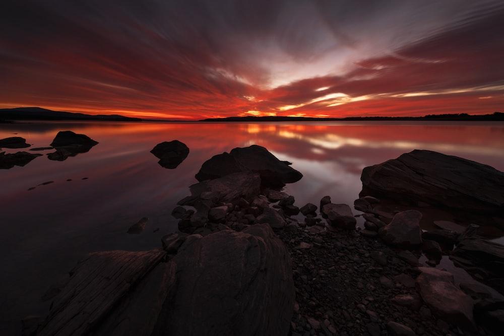 rocks in body of water during golden hour