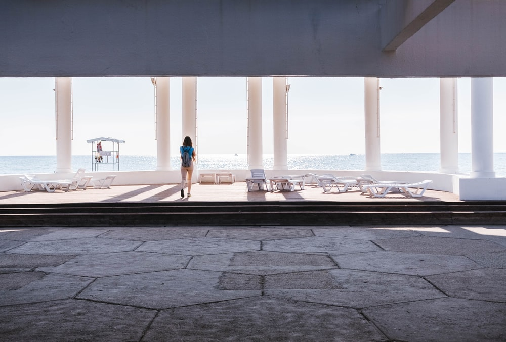 person standing outside of building overlooking sea