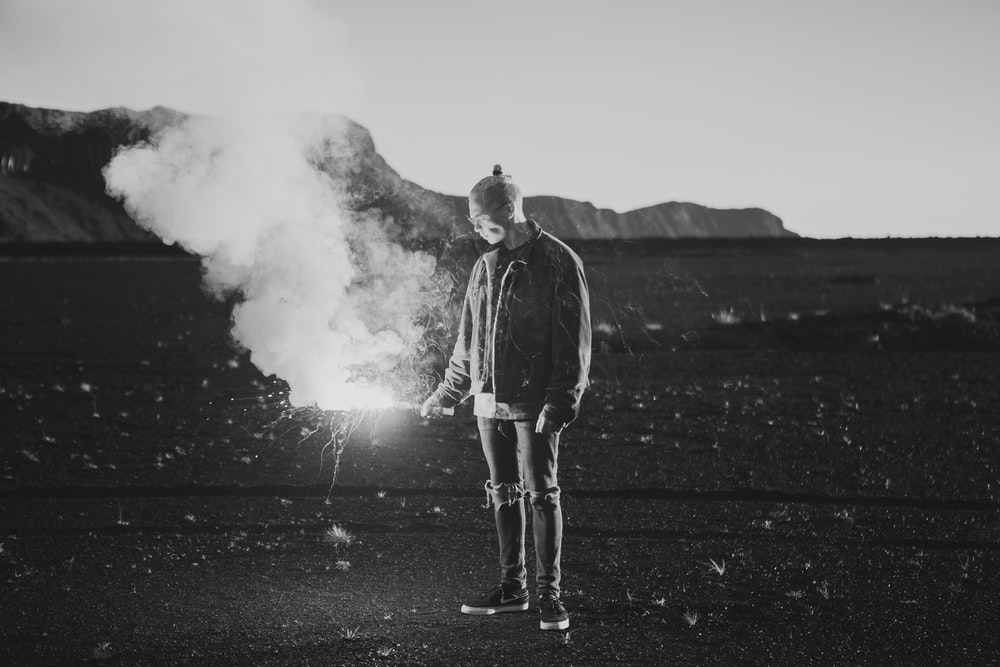 grayscale photo of man holding sparklers