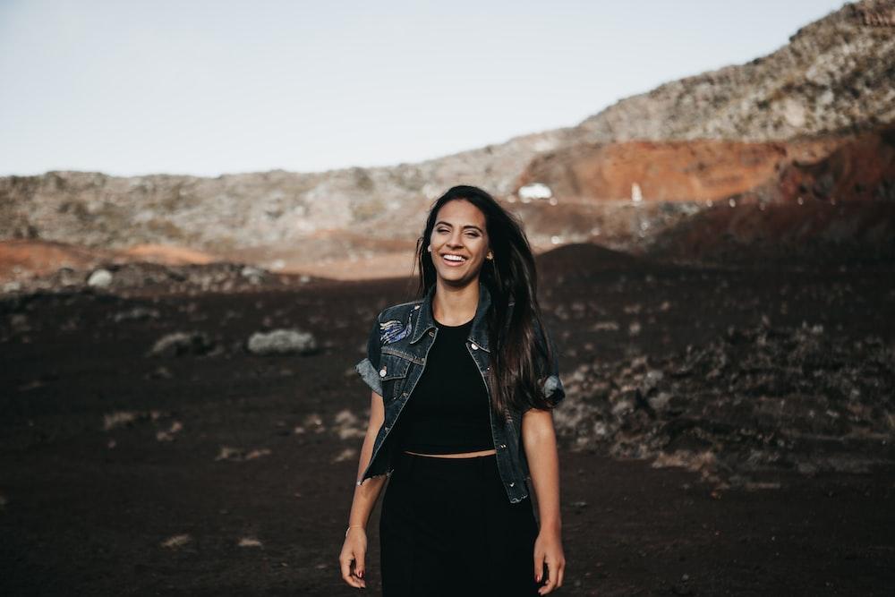 woman walking on brown sand near mountains