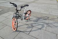 grey and orange folding bike on grey tile