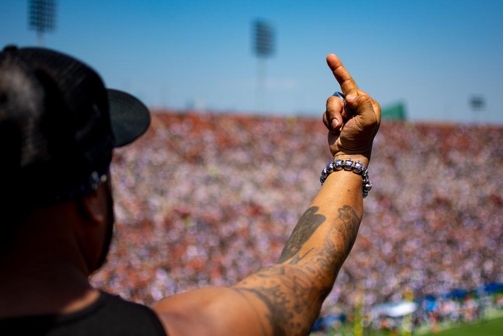 man in black tank top raising hand