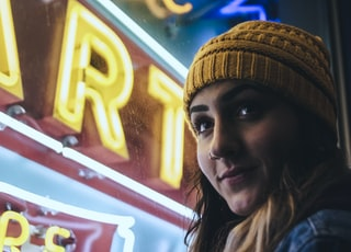 woman wearing yellow beanie while standing near neon light sign