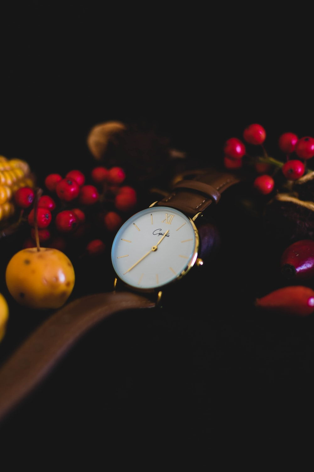 round gold-colored analog watch with leather strap near fruits