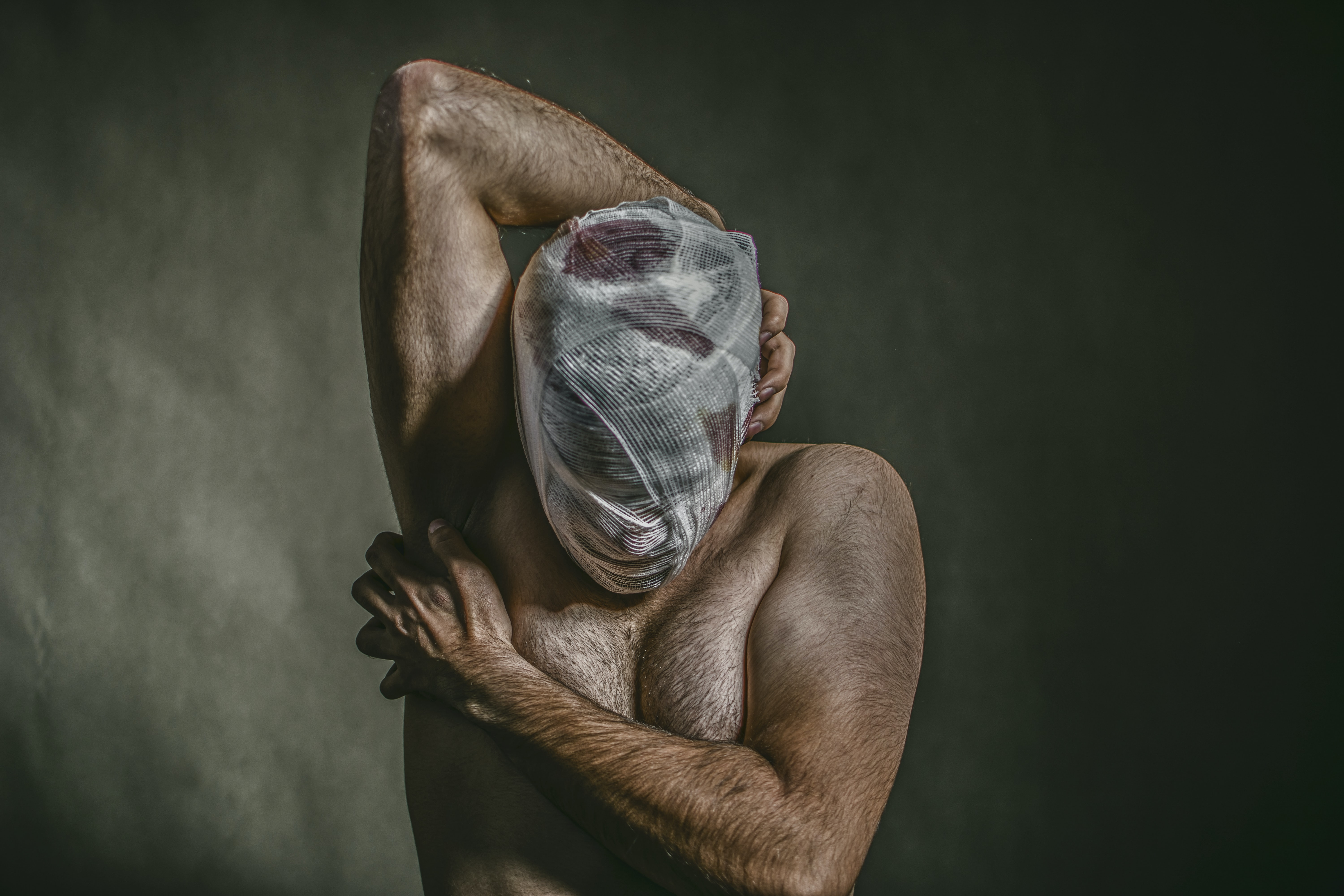 topless man covered face with white bandage