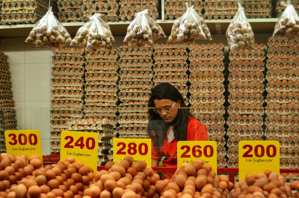 woman wearing red shirt standing beside display food