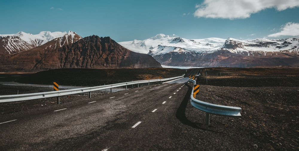 grey and white highway near lake with view of snow-capped mountain