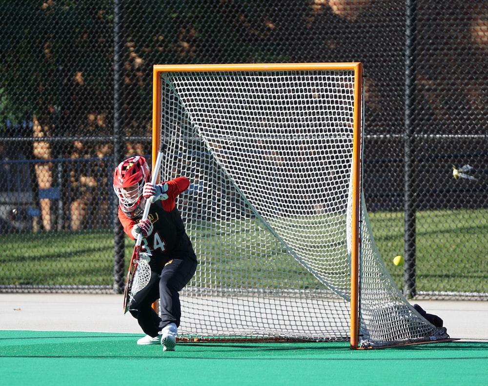 man in red helmet holding stick near goal net