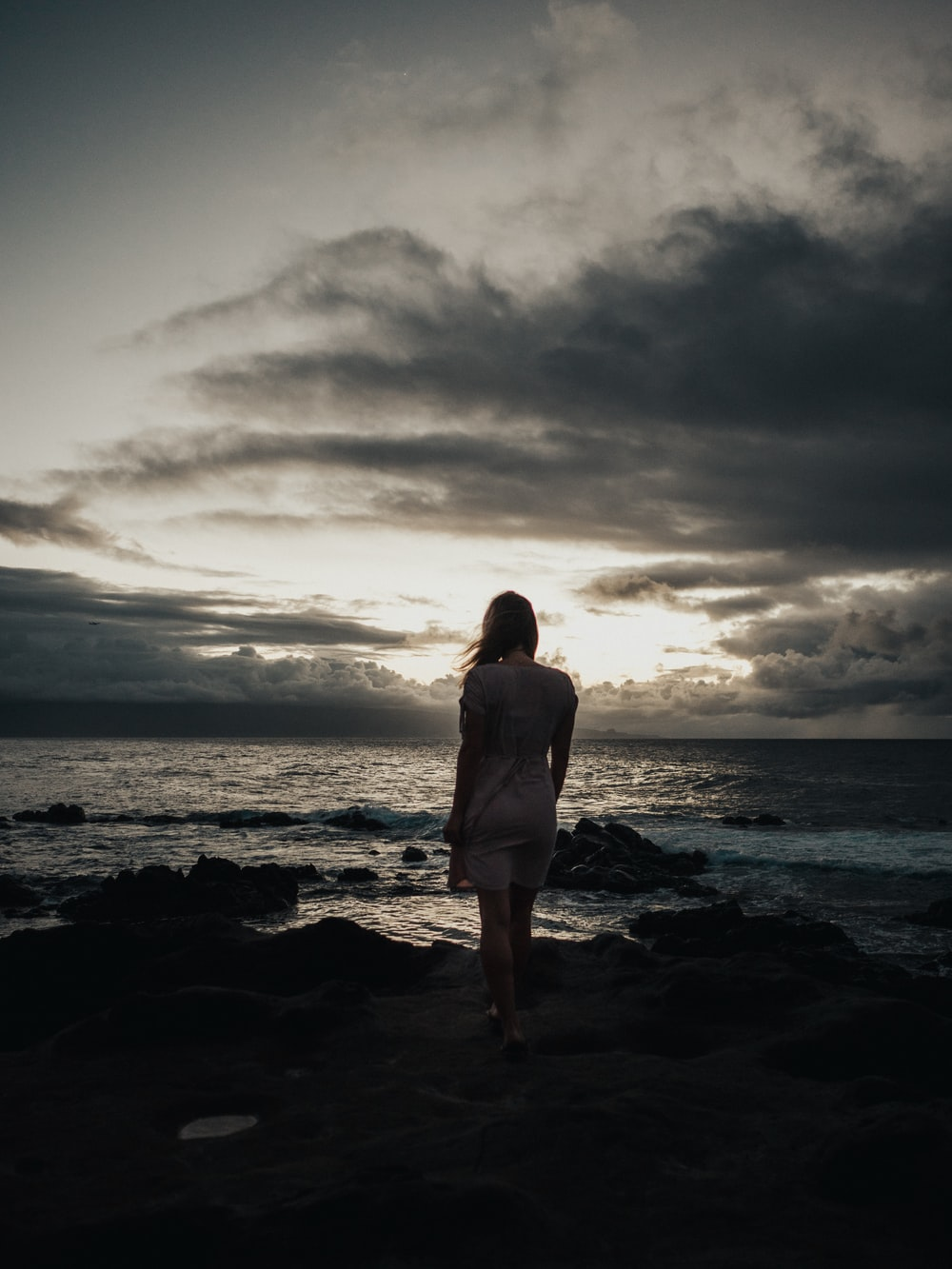 silhouette photography of woman standing near sea waves