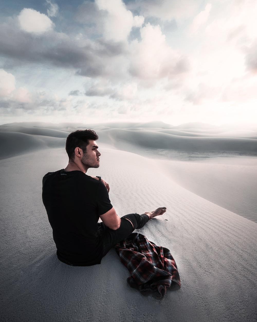 man sitting on gray sand under cloudy sky during daytime