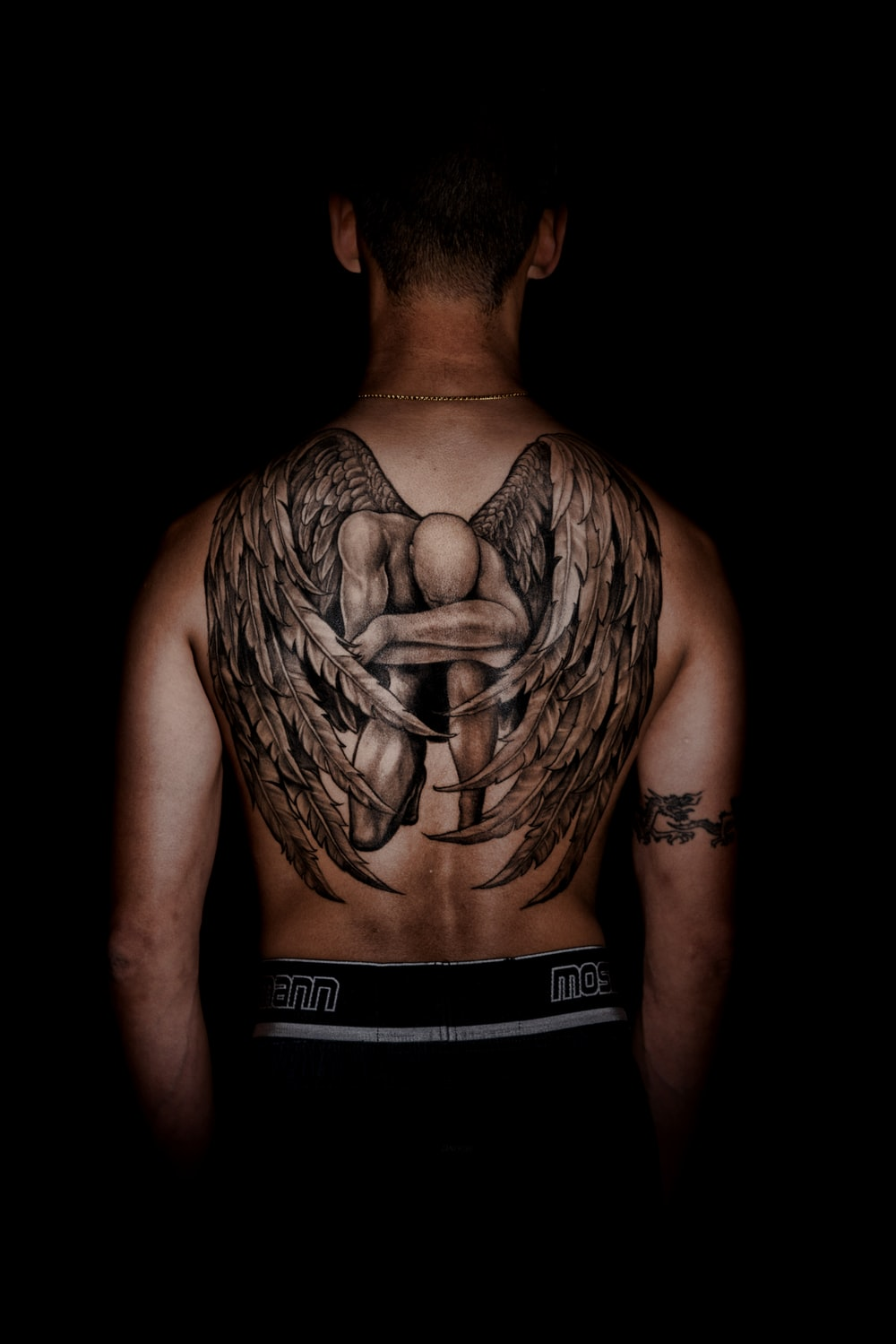 person with kneeling angel back tattoo