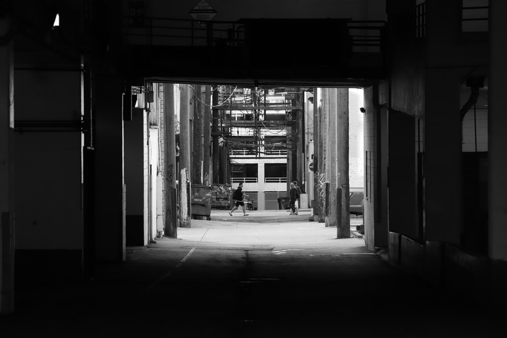 grayscale photo of man walking through tunnel