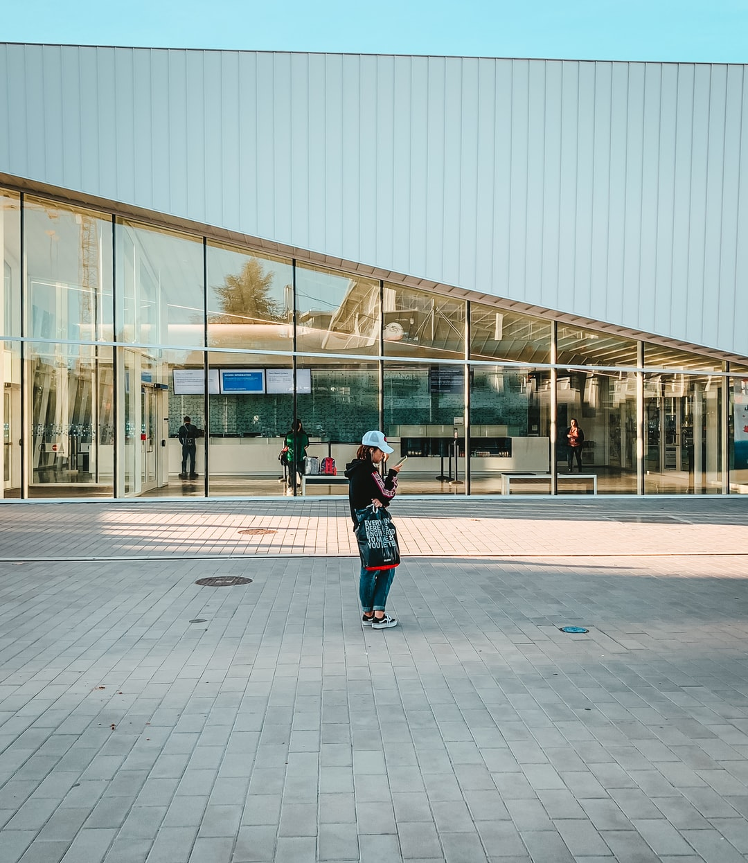 A shot of a girl looking at her phone, standing by UBC's Aquatic Center building