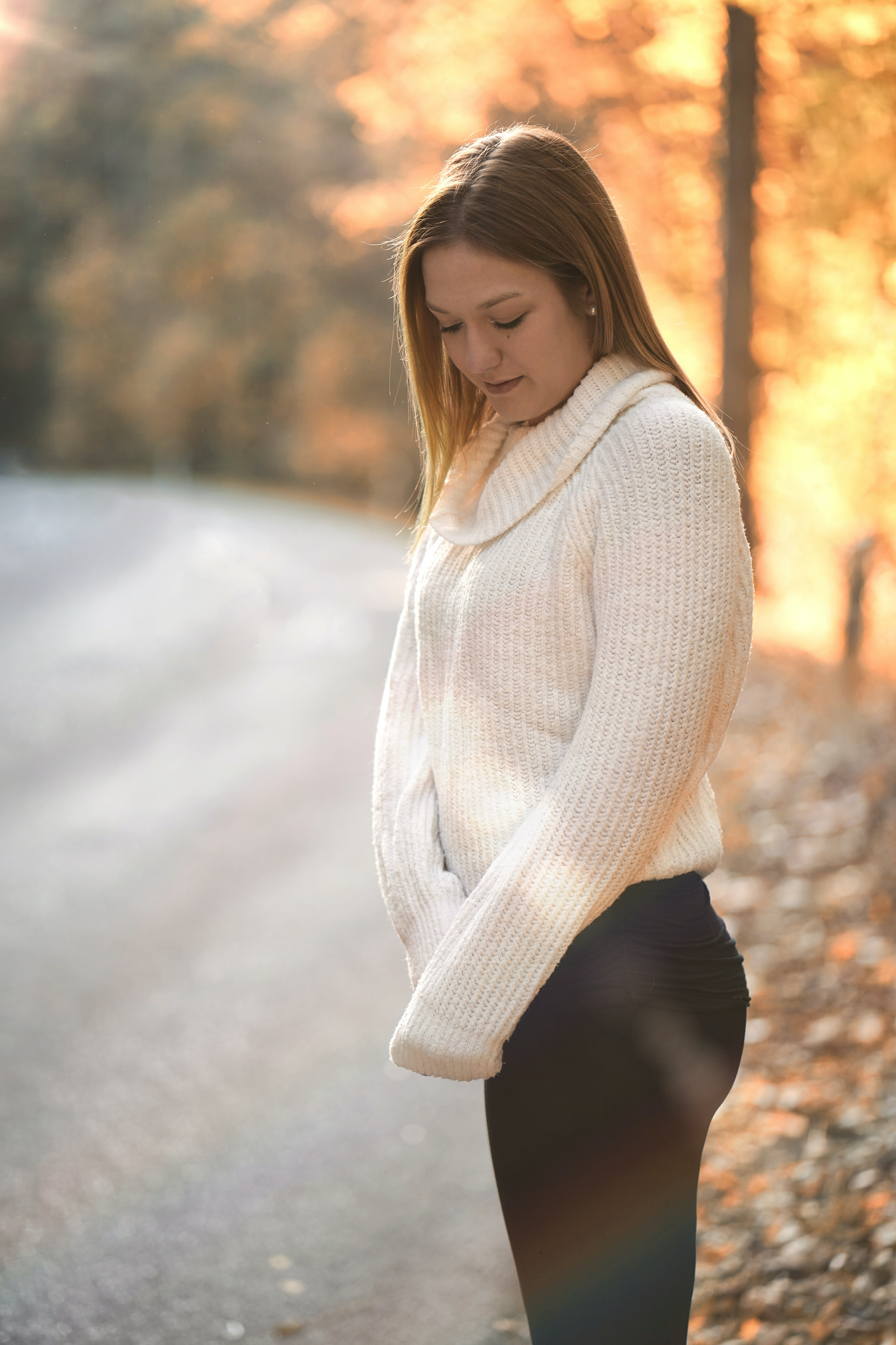 woman in white sweater standing outdoor