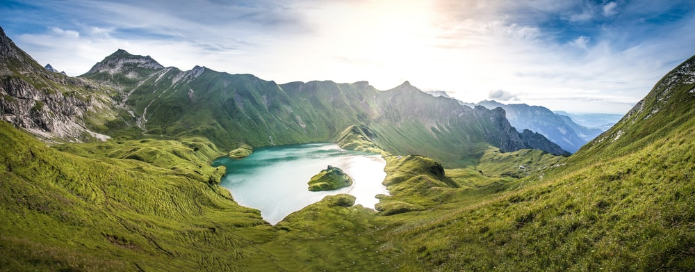 green mountains near lake